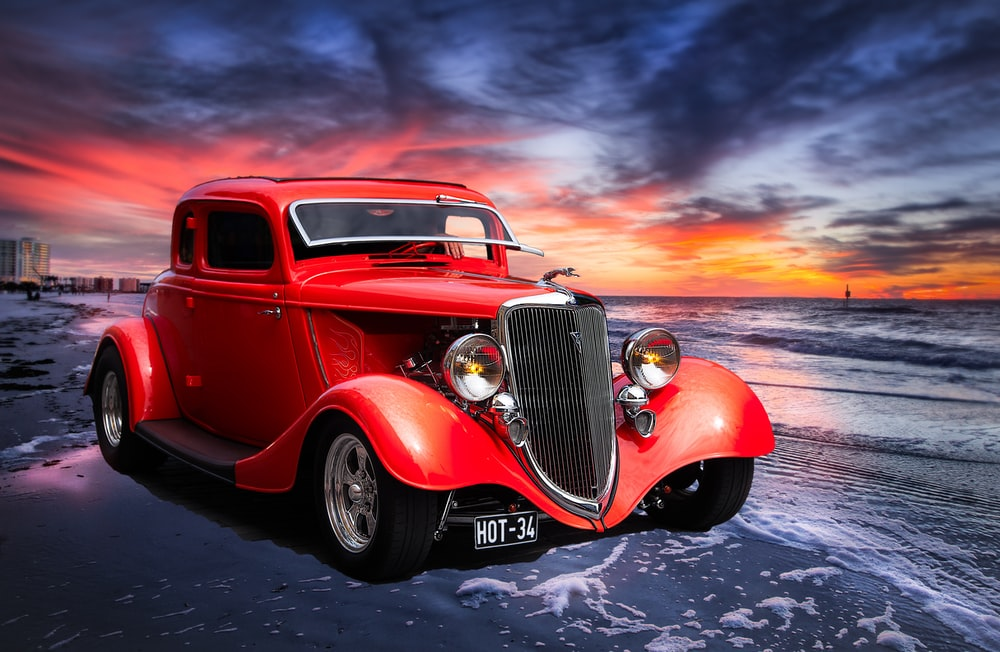 red classic car on road