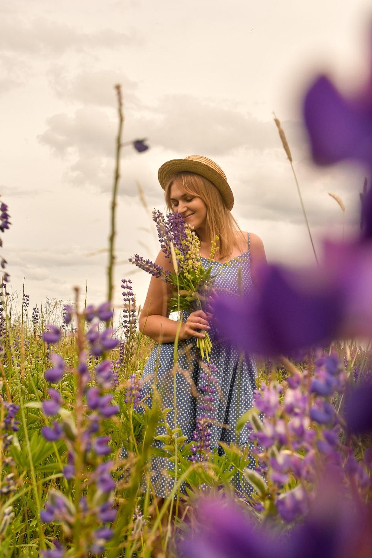 woman in purple and white polka dot dress wearing brown hat standing on purple flower field