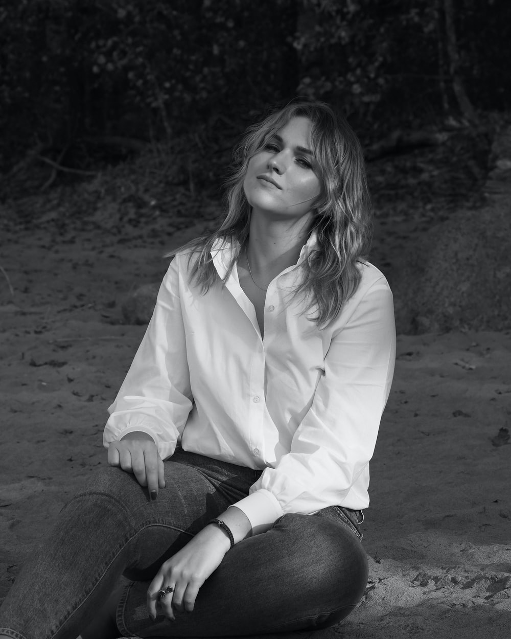 woman in white dress shirt and black denim jeans sitting on ground