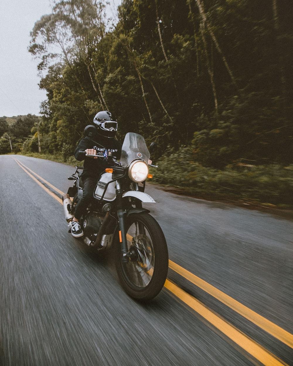 man in black helmet riding motorcycle on road during daytime