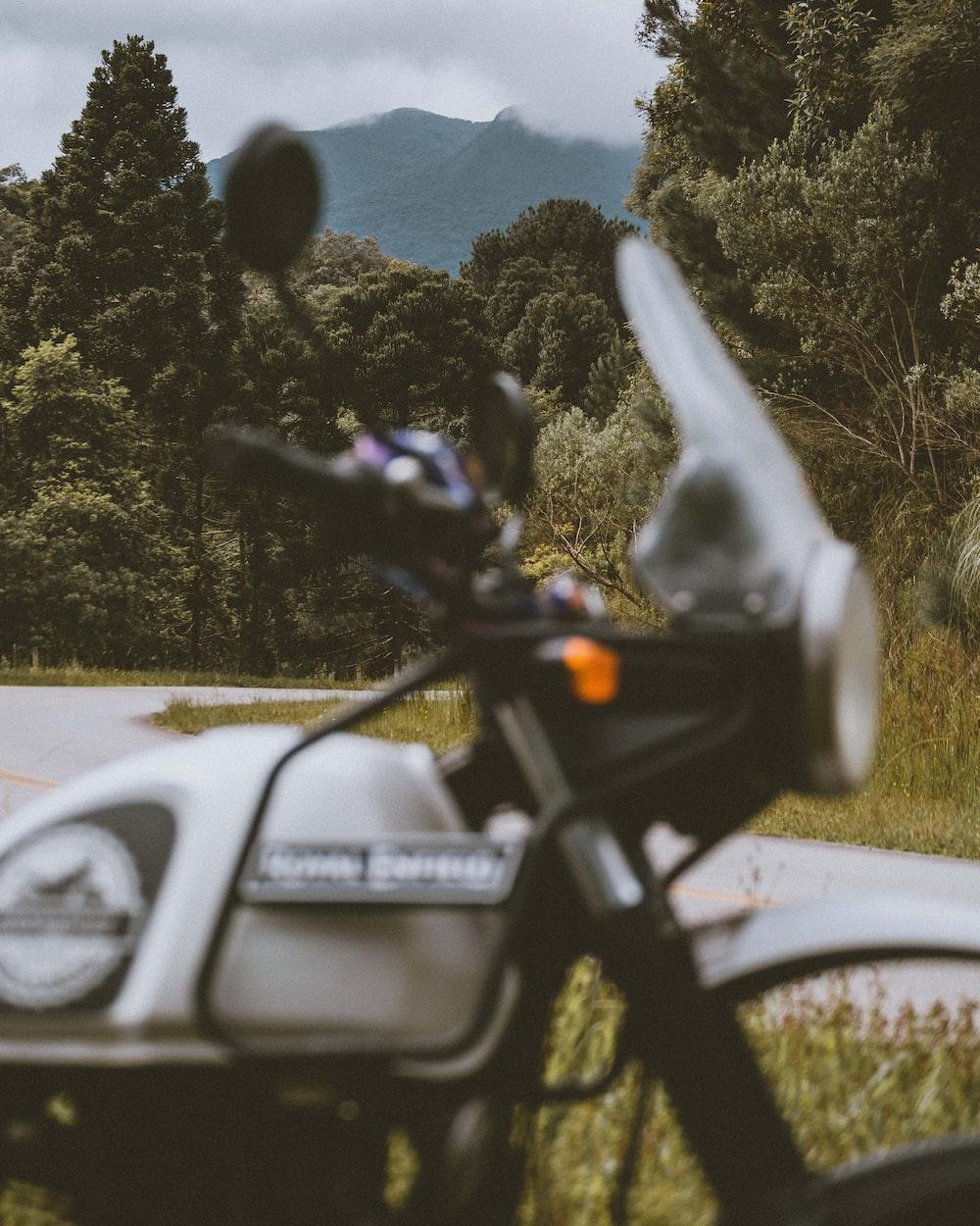 white honda motorcycle parked on gray asphalt road during daytime
