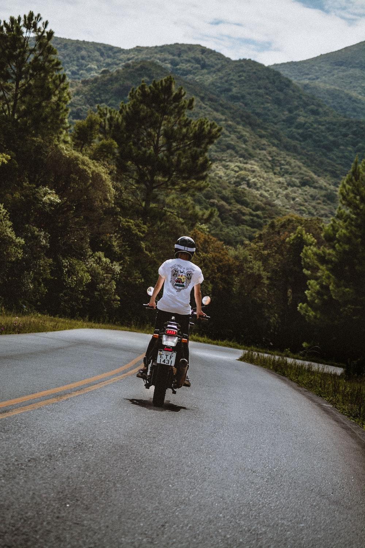 man in white t-shirt riding bicycle on road during daytime