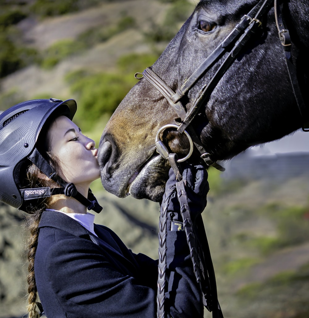 man in black jacket wearing black helmet riding brown horse during daytime