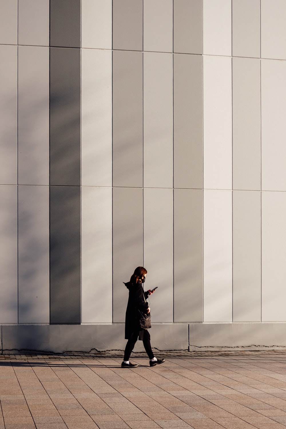 woman in black coat standing beside white and blue wall