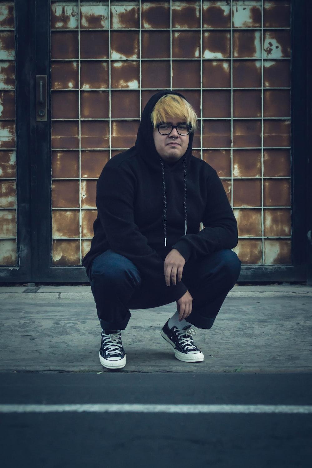 man in black hoodie and blue denim jeans sitting on brown brick wall