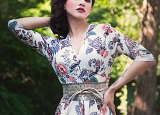 woman in white blue and red floral dress standing on brown wooden bridge during daytime