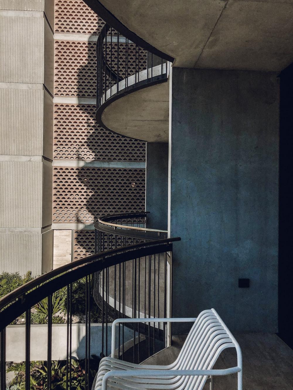 black metal spiral staircase near brown concrete building during daytime