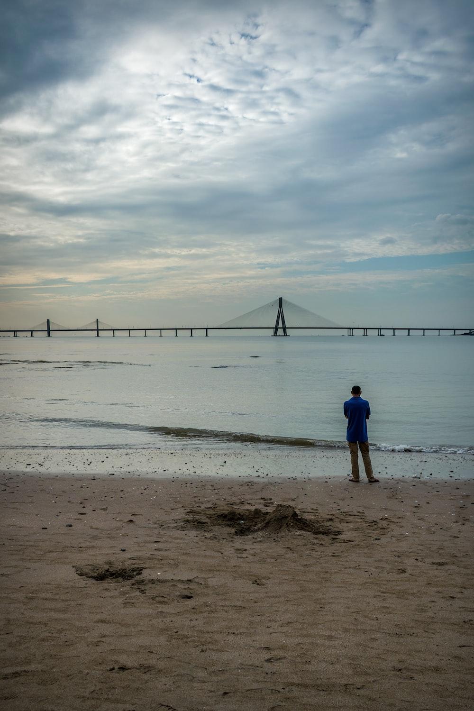 man in blue shirt walking on beach during daytime