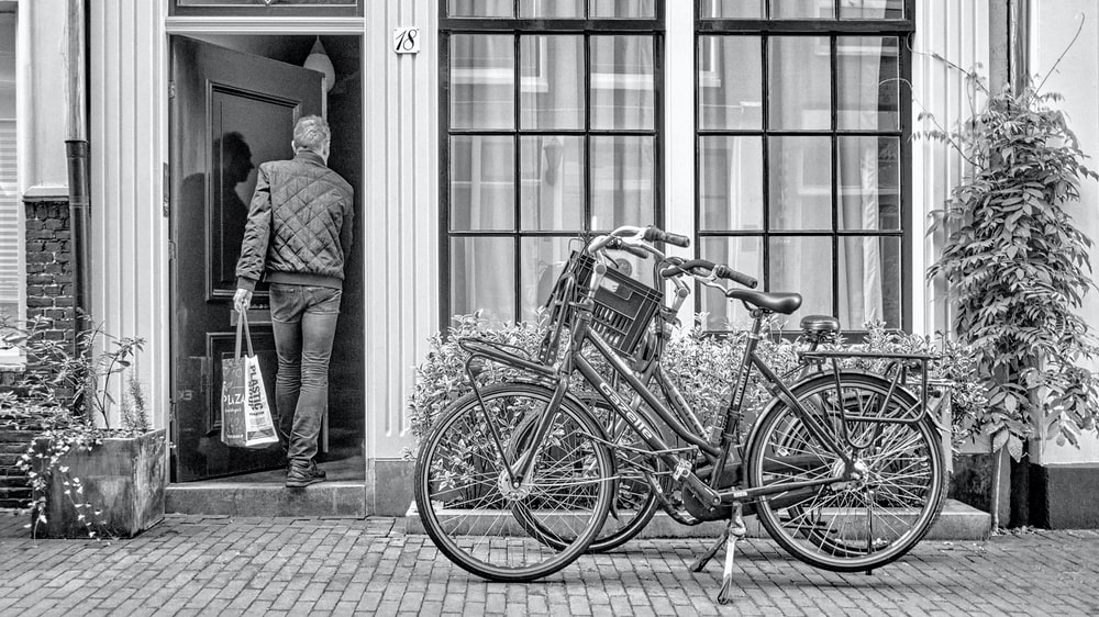 grayscale photo of man in suit standing beside bicycle