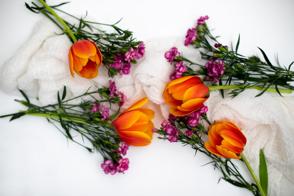 yellow and pink tulips on white textile
