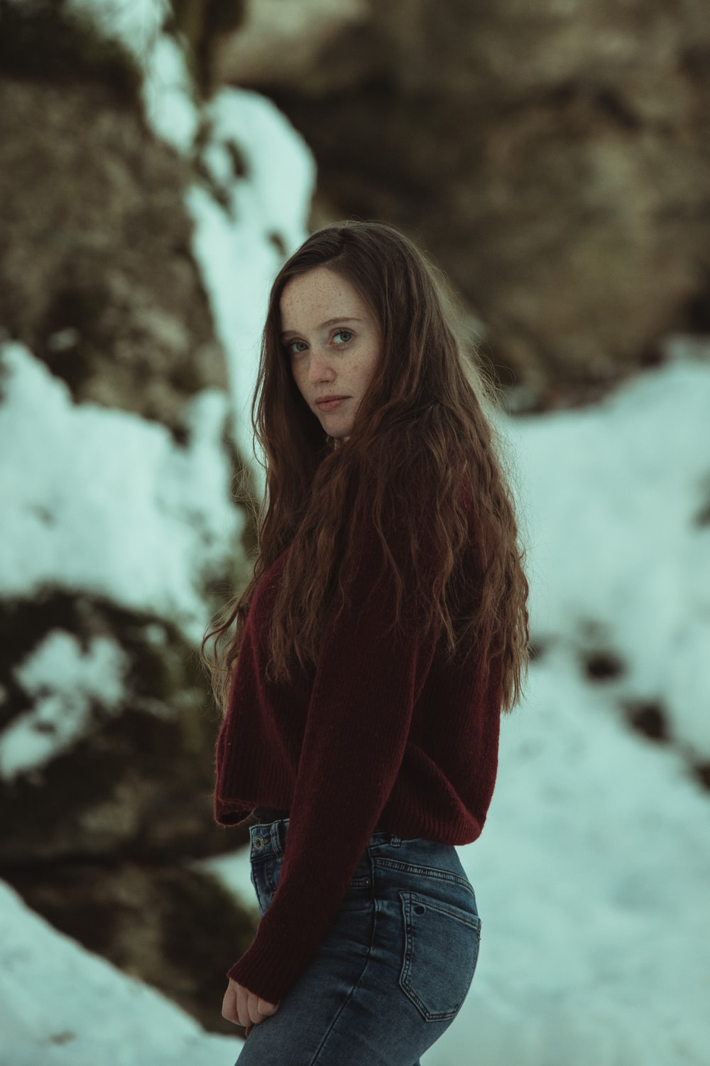 woman in red long sleeve shirt and blue denim jeans standing on snow covered ground during