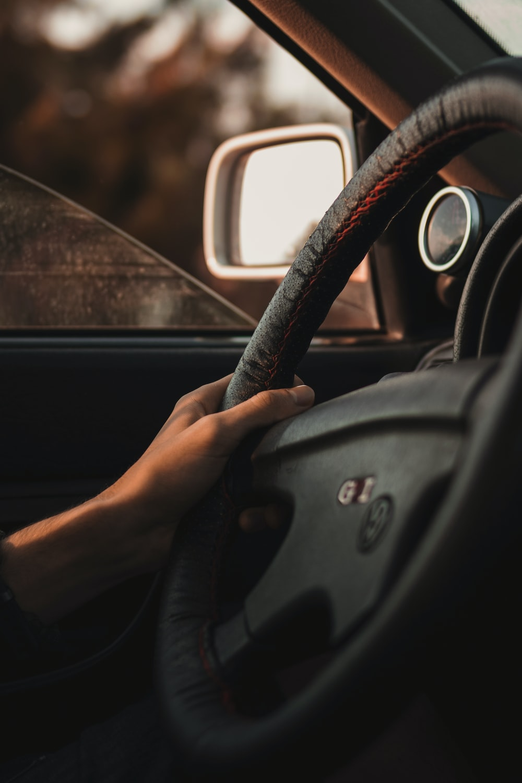 person holding black steering wheel