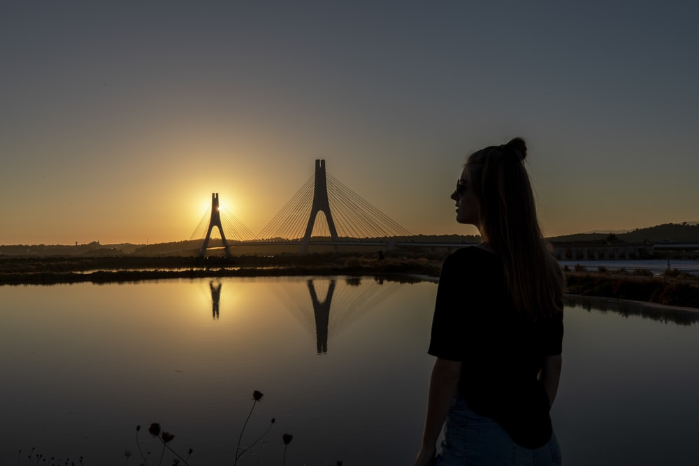 silhouette of woman standing on dock during sunset