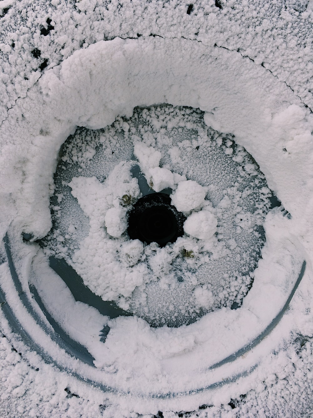 grayscale photo of hole in the middle of snow