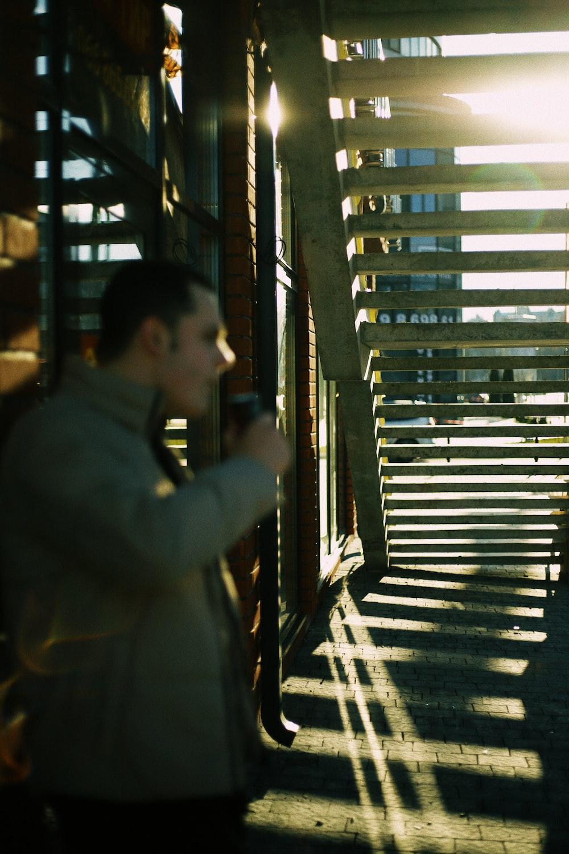 man in black jacket standing near brown wooden door