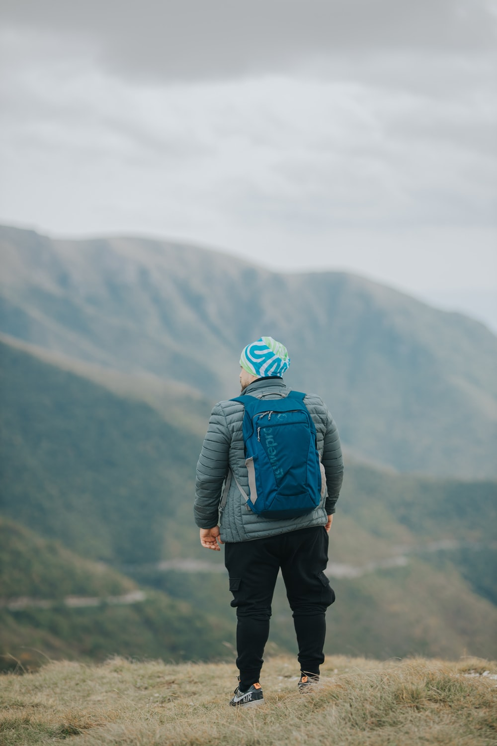 man in blue jacket and black pants with backpack standing on top of mountain during daytime