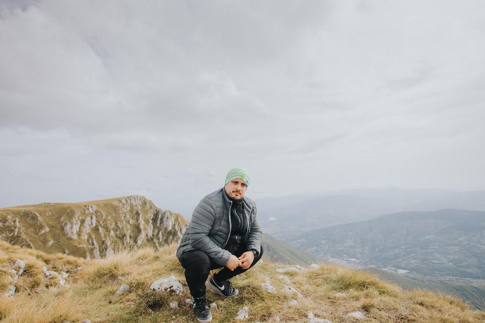 man in black jacket sitting on rock formation during daytime