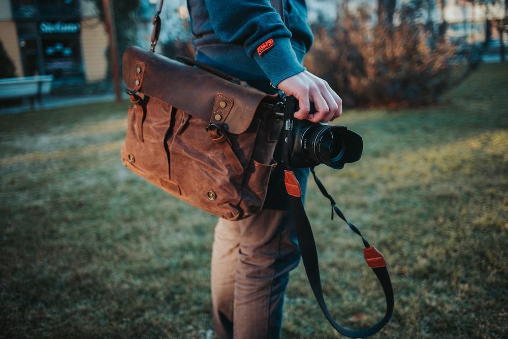 person in blue jacket holding black dslr camera