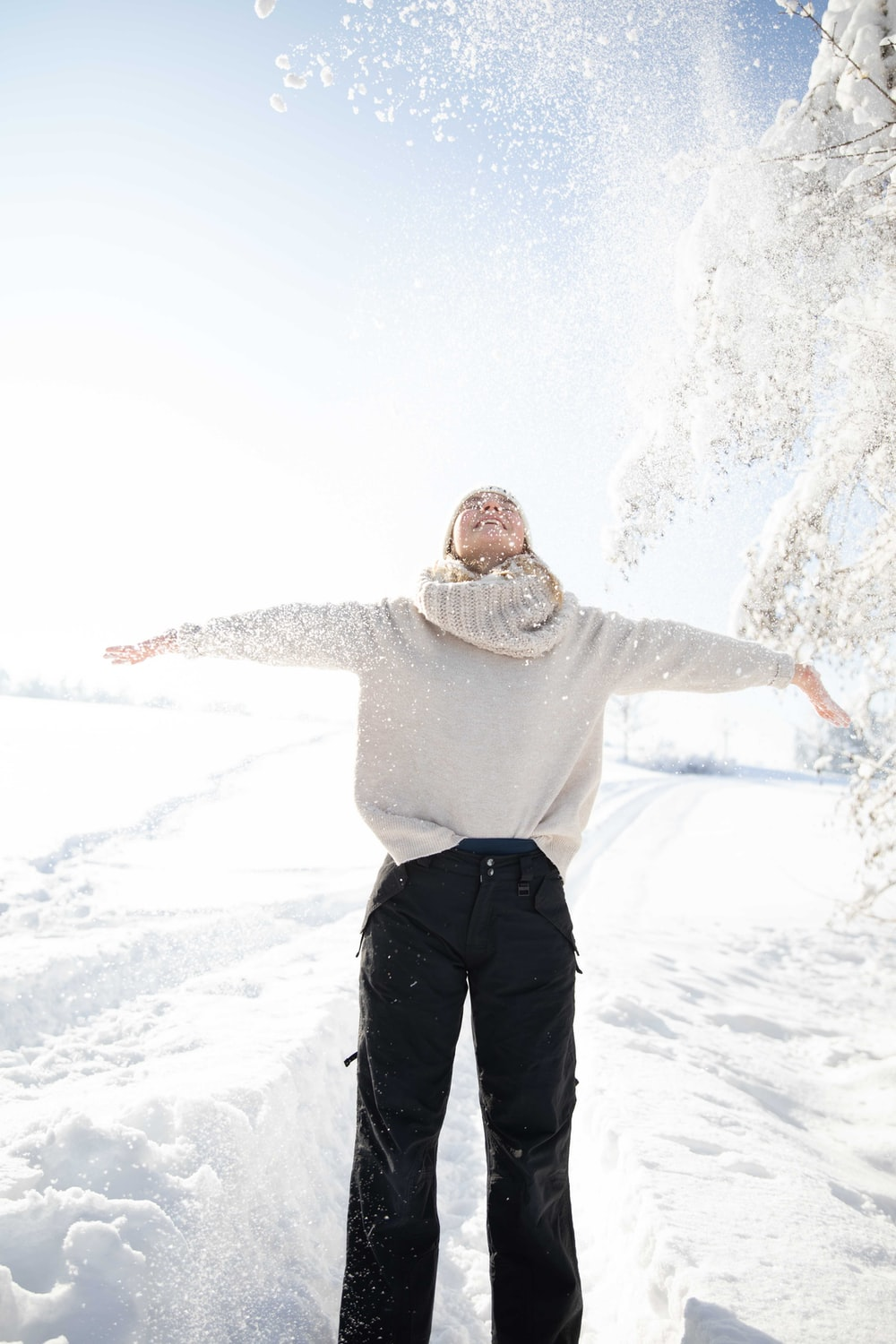 man in gray hoodie and black pants standing on snow covered ground during daytime
