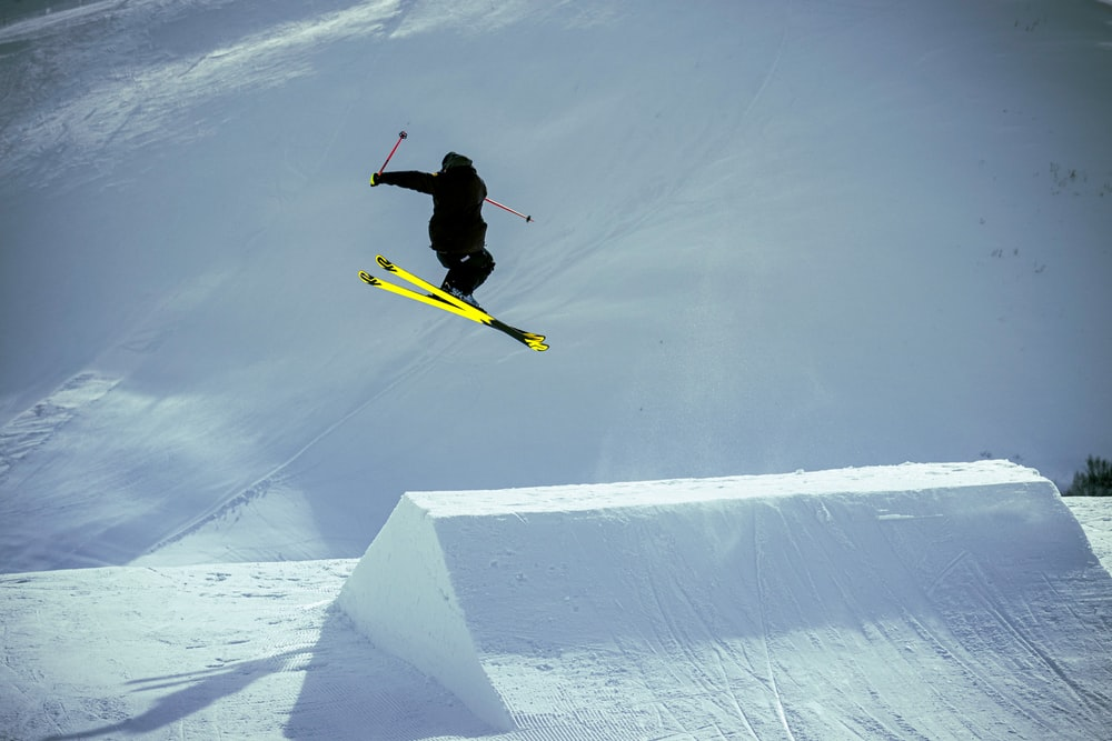 man in black jacket and yellow pants riding yellow snowboard on snow covered ground during daytime