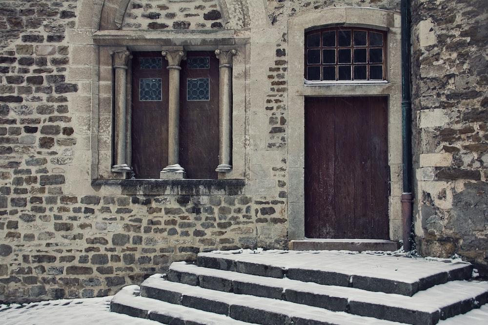 brown wooden door on brown brick building