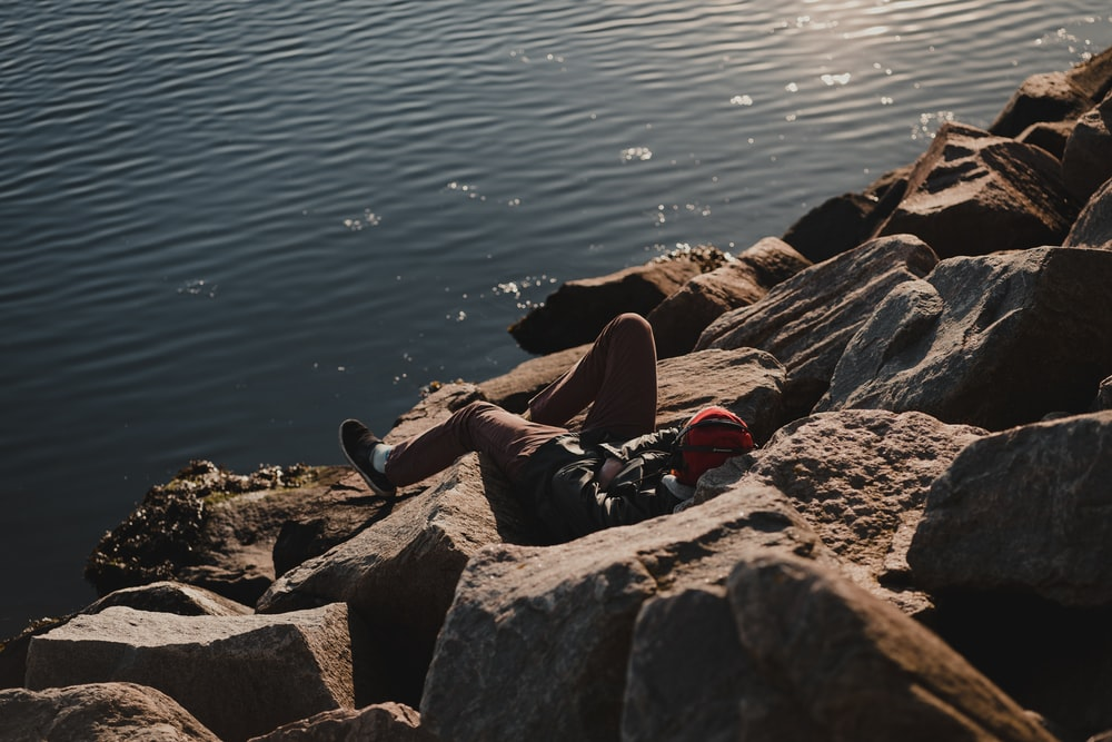 person in black pants sitting on gray rock near body of water during daytime