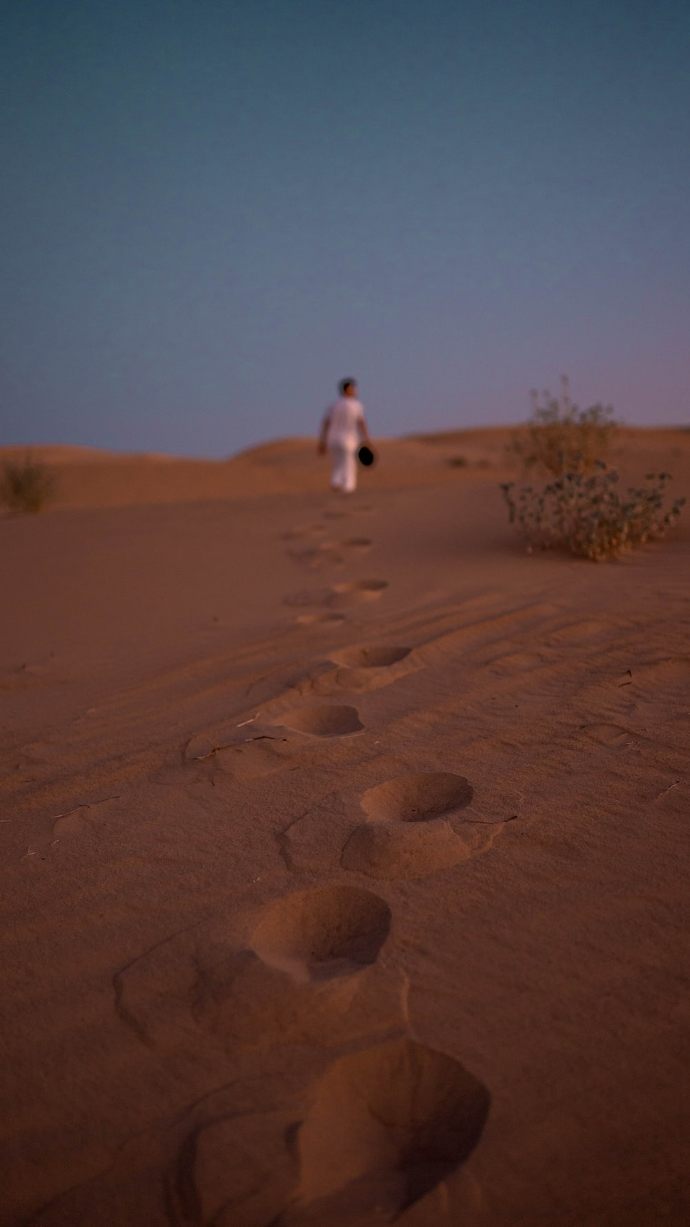 person in white shirt walking on brown sand during daytime