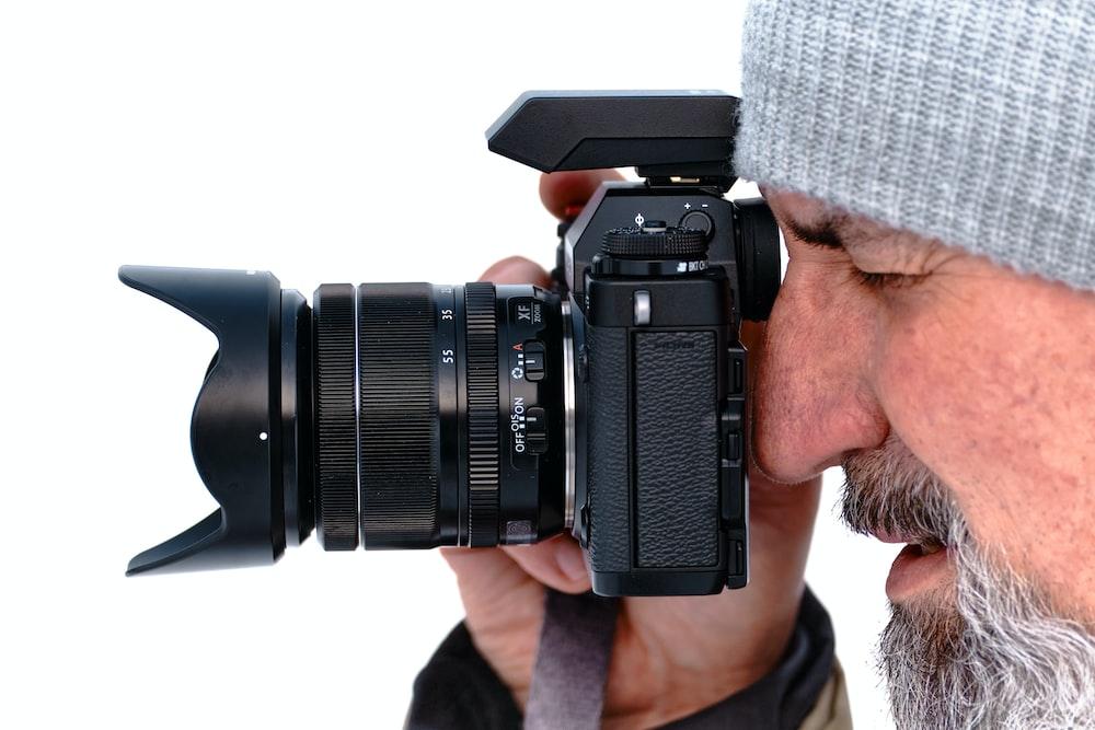 man in gray knit cap holding black dslr camera
