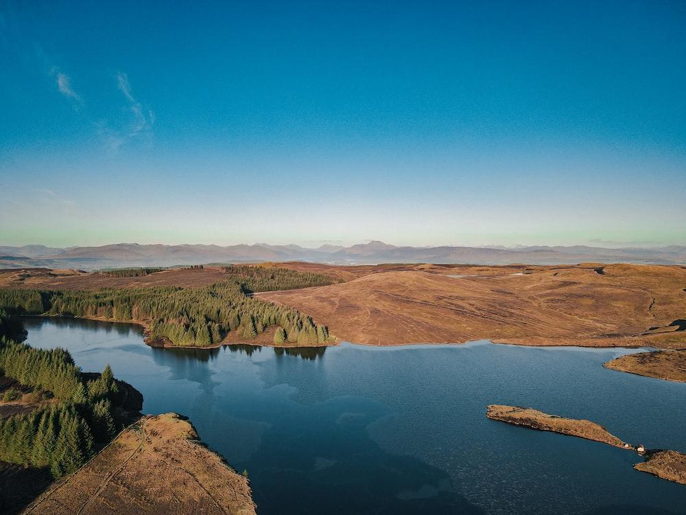 brown mountains near lake under blue sky during daytime