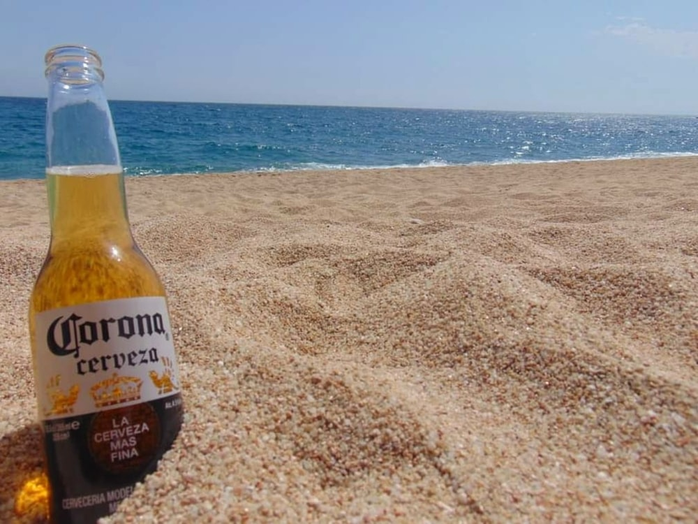brown and white labeled bottle on brown sand near sea during daytime