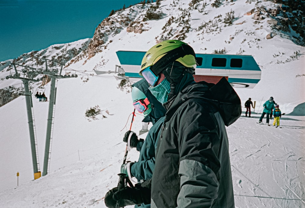 person in black jacket and green helmet on snow covered mountain during daytime