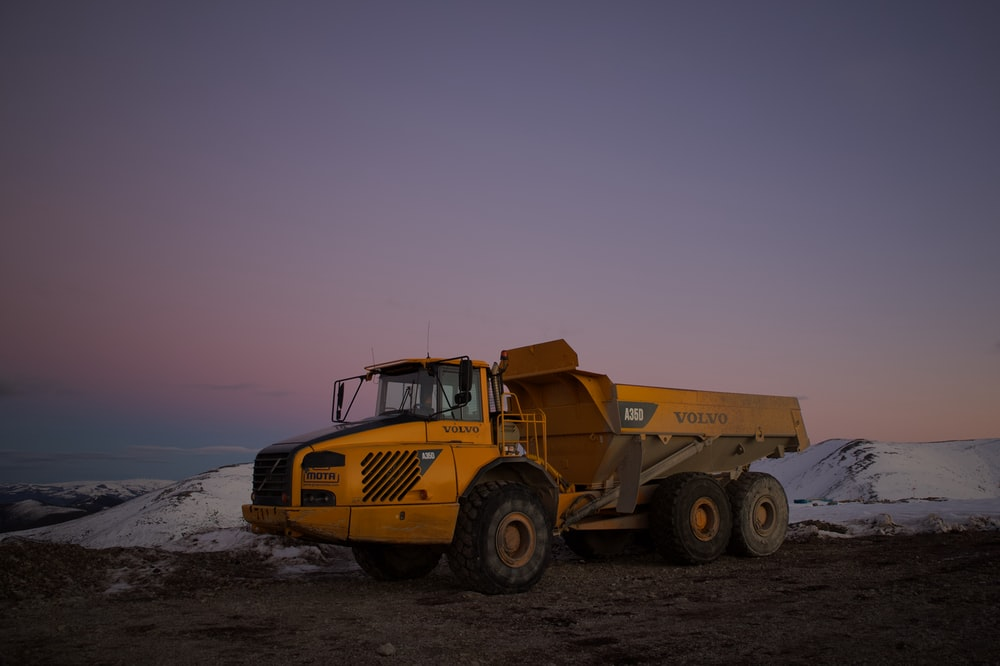 yellow and black heavy equipment on snow covered ground during daytime