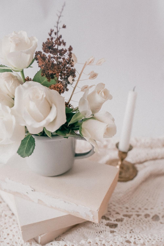 white roses in white ceramic mug