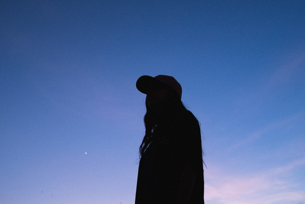 silhouette of woman wearing hat under blue sky during daytime