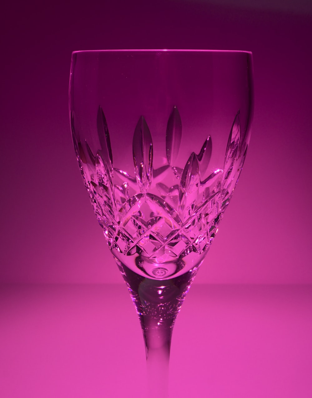 red wine glass on pink surface