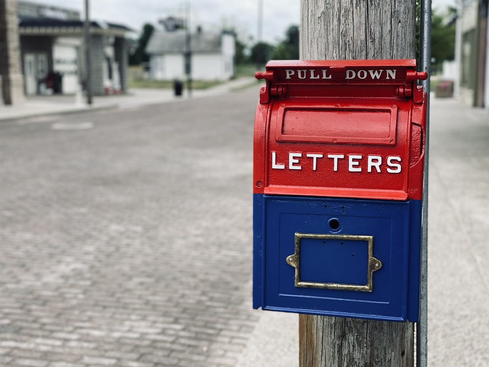 red mail box on brown wooden post