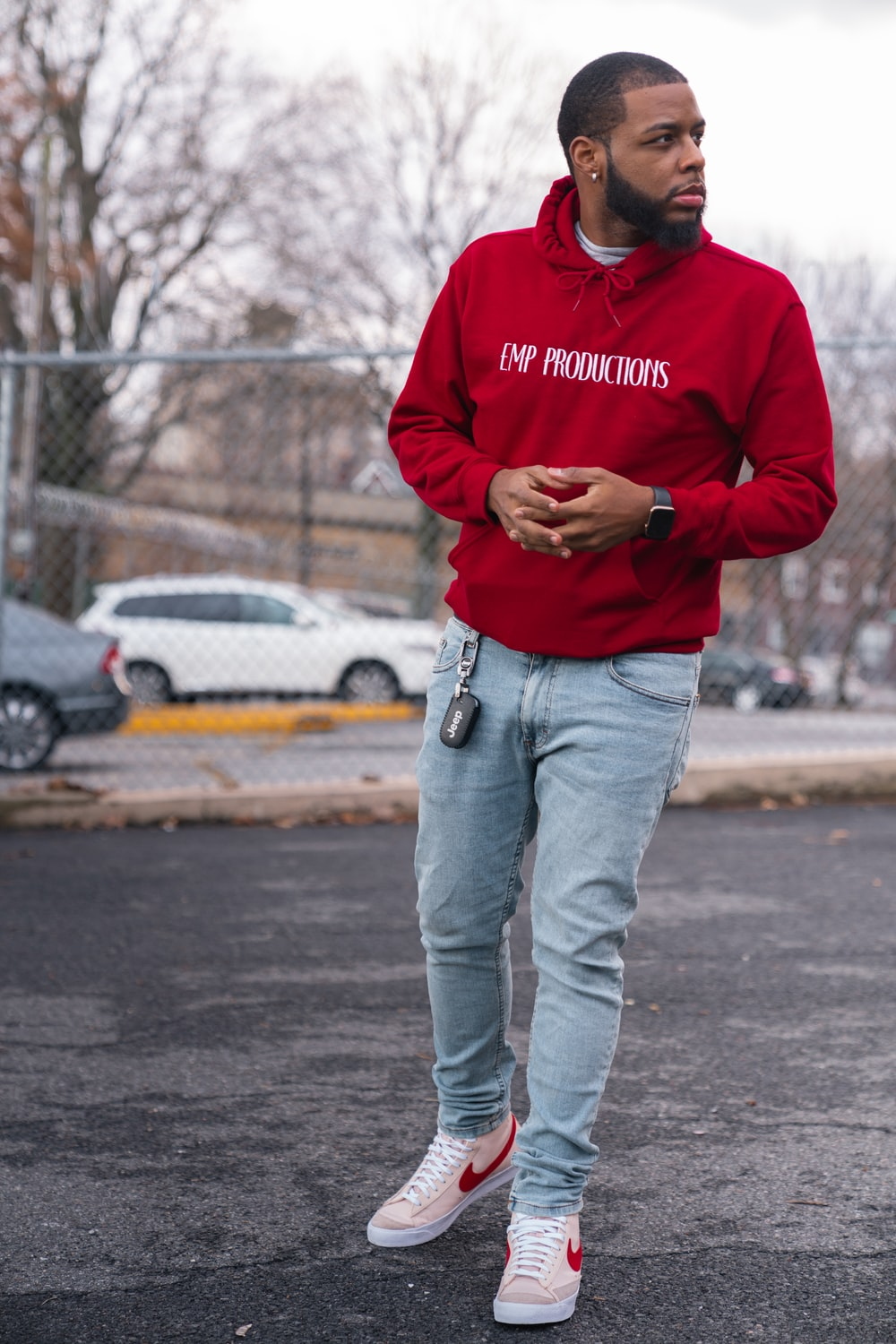 man in red hoodie and blue denim jeans standing on road during daytime
