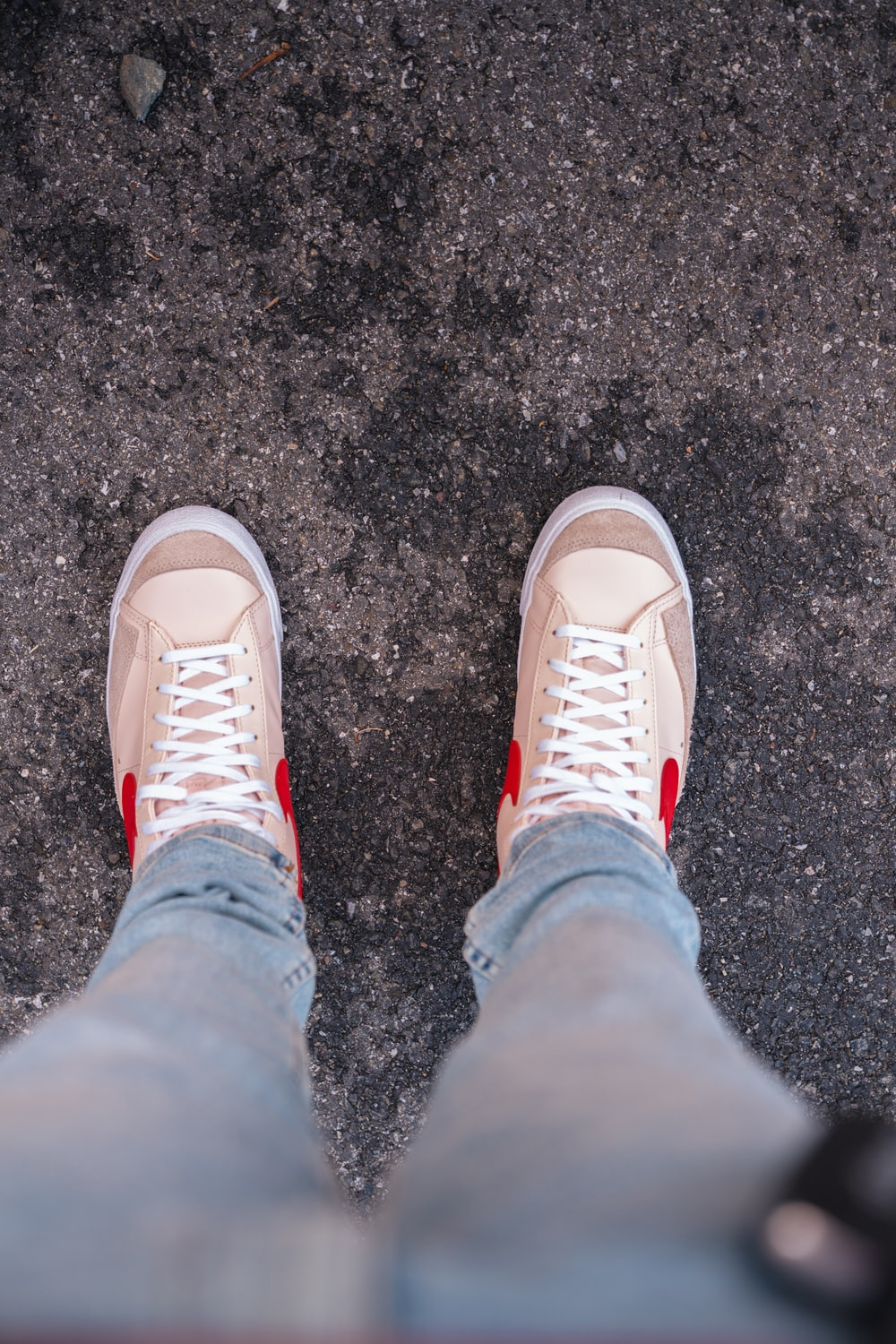 person in blue denim jeans and white sneakers