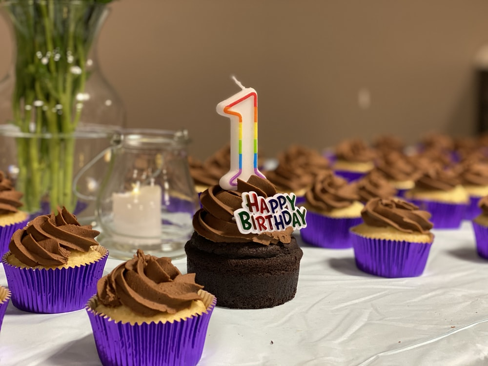 chocolate cupcake with pink and purple candles