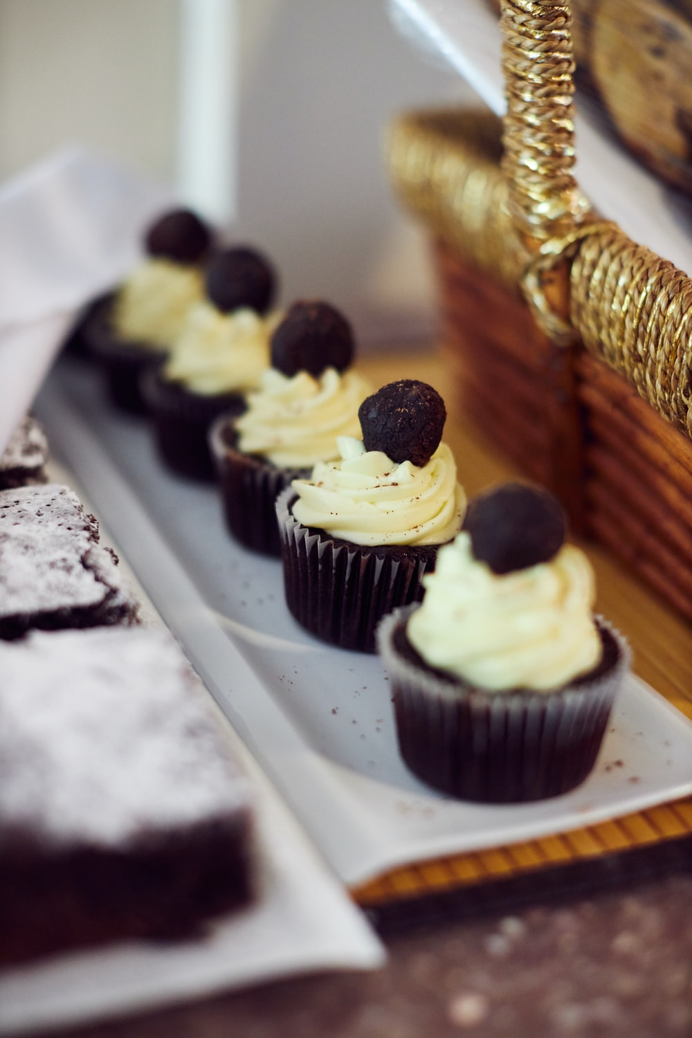 white and black cupcakes on brown wooden tray