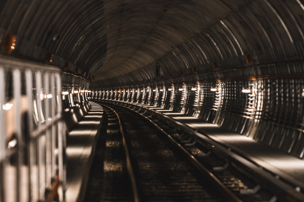 black train rail in tunnel