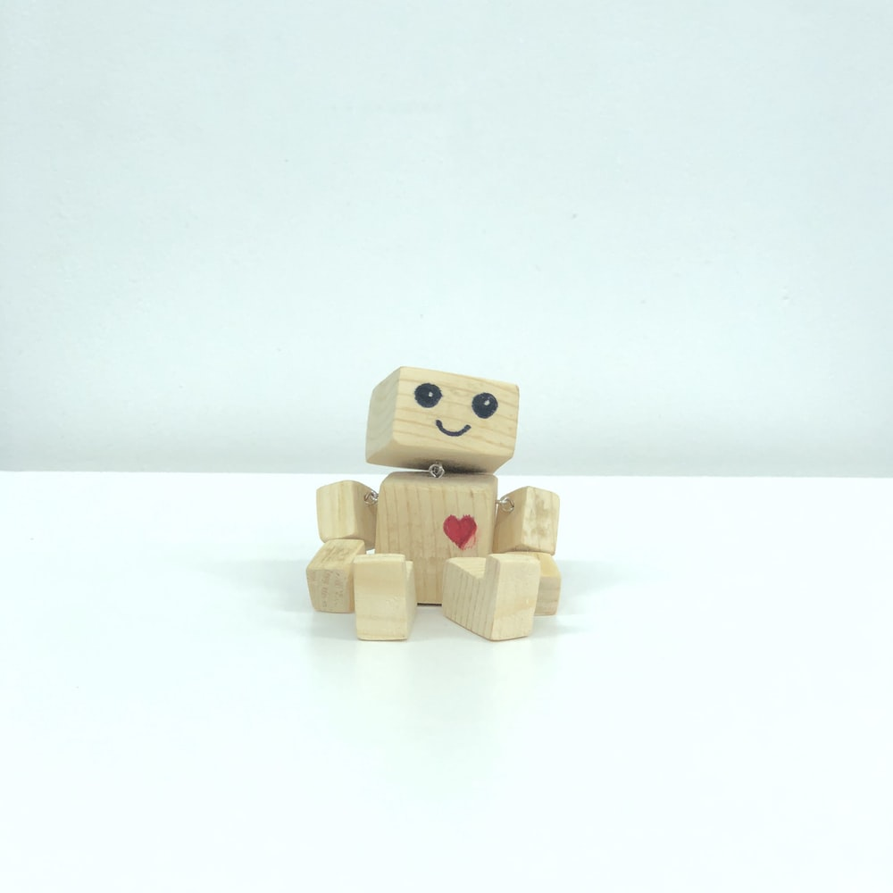 brown wooden robot toy on white surface