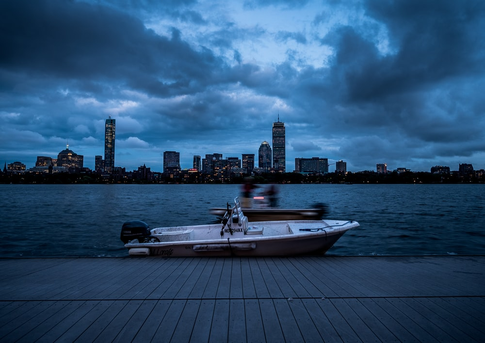 white and black boat on sea dock near city buildings under cloudy sky during daytime