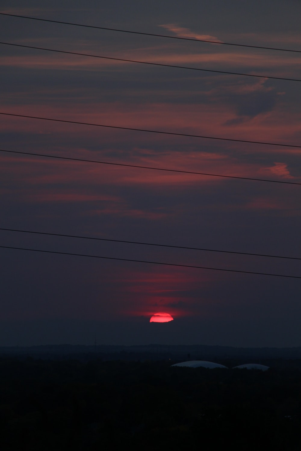 red hot air balloon over the clouds during sunset