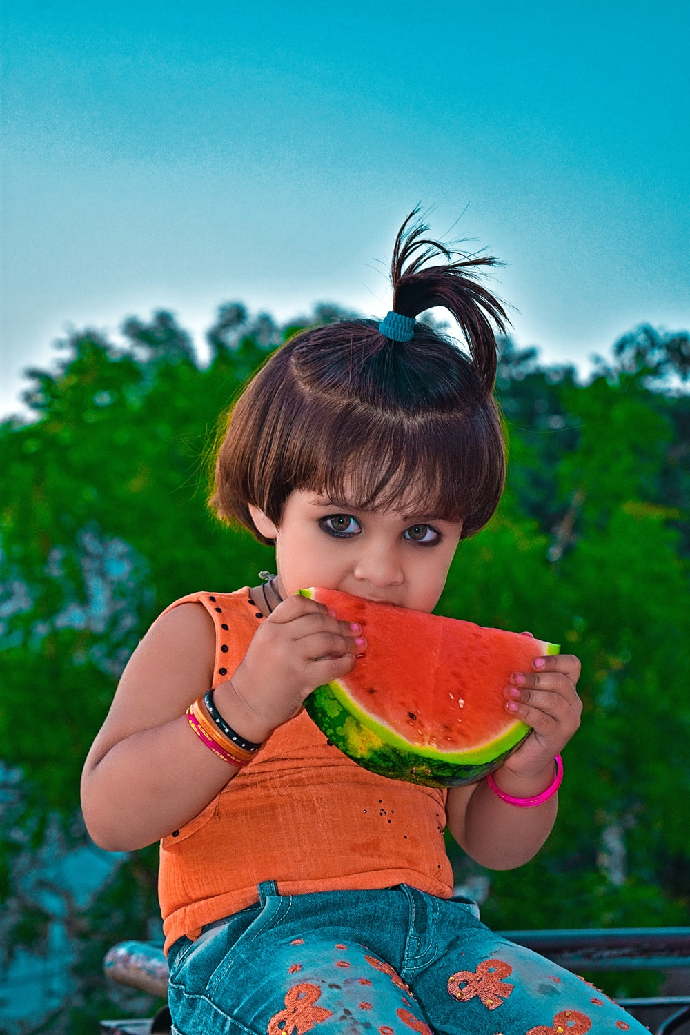 girl in pink tank top eating watermelon