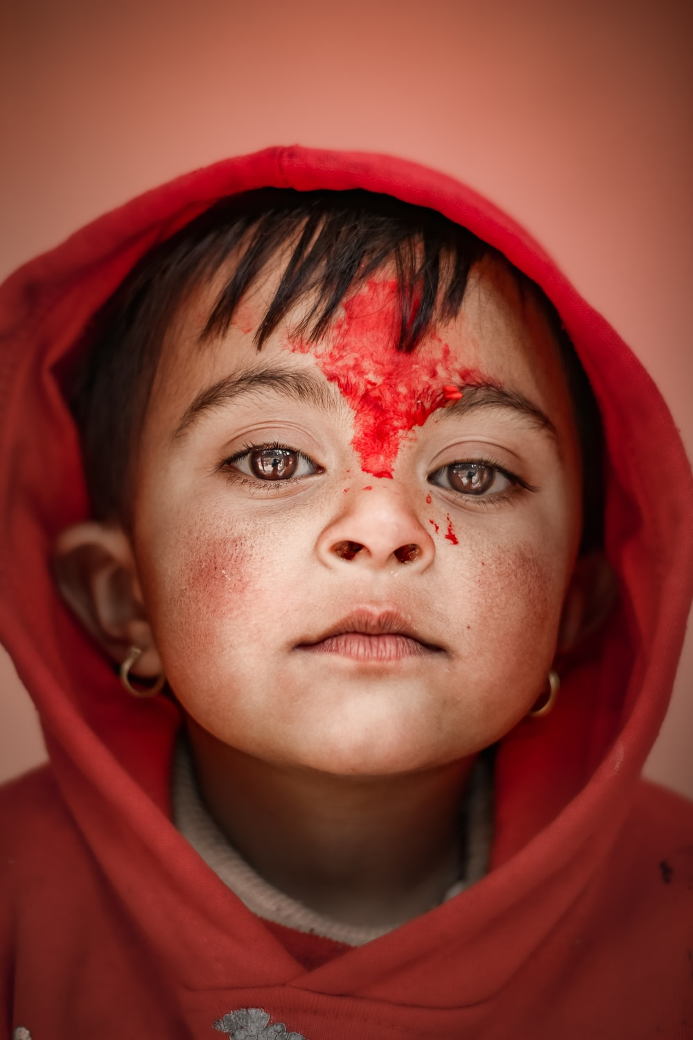 woman in red hoodie with red powder on face