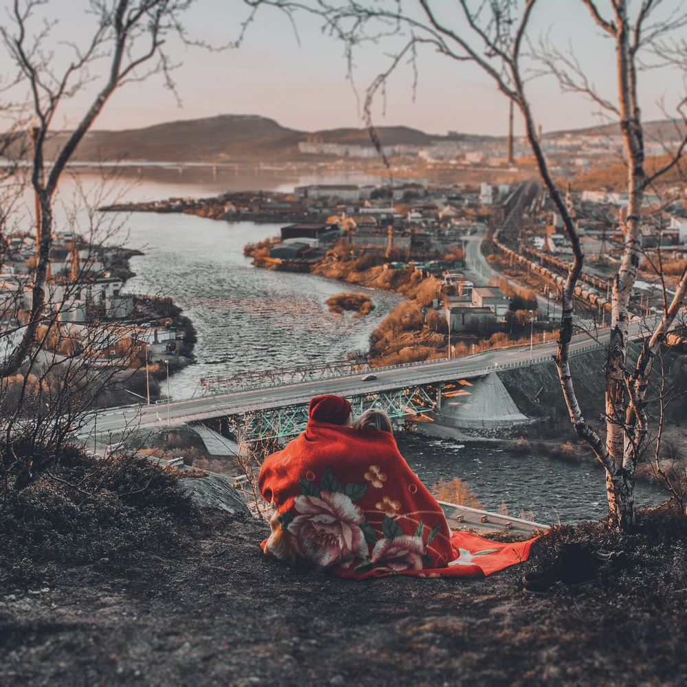 person in red hoodie sitting on rock near body of water during daytime
