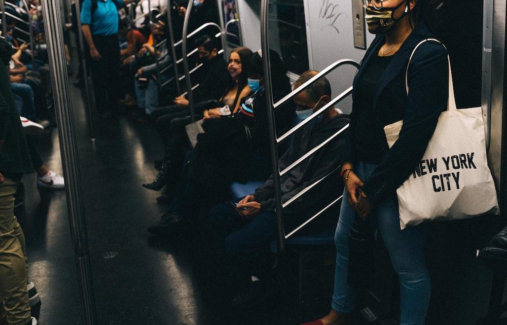 man in black jacket and blue denim jeans standing beside woman in black jacket