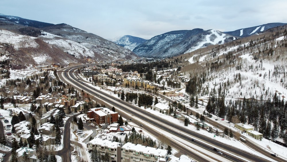 aerial view of city near snow covered mountains during daytime