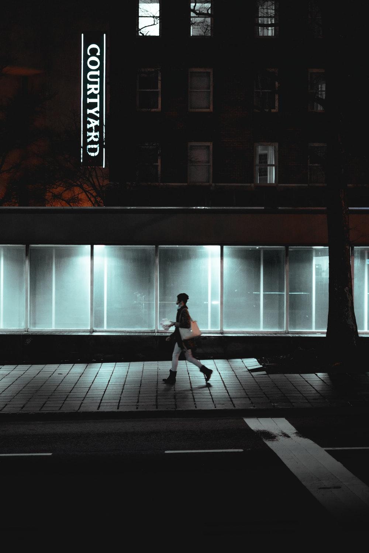 woman in white dress walking on sidewalk during daytime